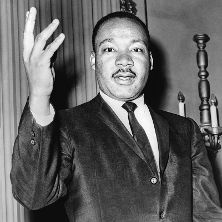 Martin Luther King speaking with his right hand in the air.