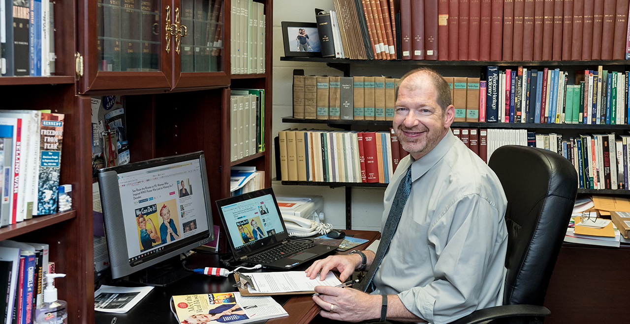 Professor James J. Kimble of the College of Communication and the Arts working in his office.