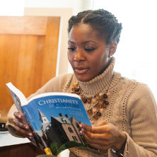 Student reading Christianity and Culture in Dialogue book in the library for the Core Curriculum.
