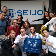 Students in Japan pointing at a Seton Hall flag.