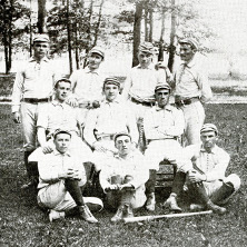 Ten men are posed for the baseball team photo in three different rows. The photo is outside and there is a wooden bat in front of them.